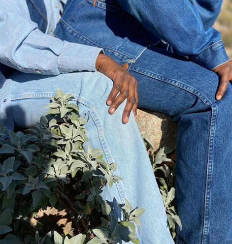 Two people sitting close together, one with light blue denim top and bottom, and the other with true blue denim top and bottom. there are some green plants in the bottom left corner.