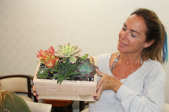 Woman Holding succulent arrangement at orange county plater box workshop