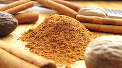 a pile of brown spices surrounded by cinnamon sticks