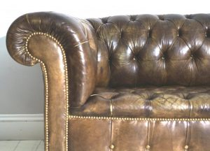close up of the antique brown leather chesterfield sofa