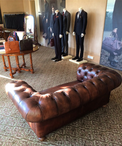 manquins next to a chesterfield sofa