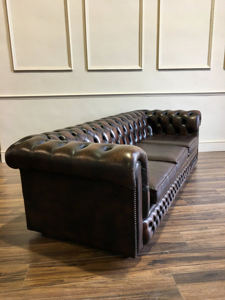Arm of dark brown leather Chesterfield Sofa