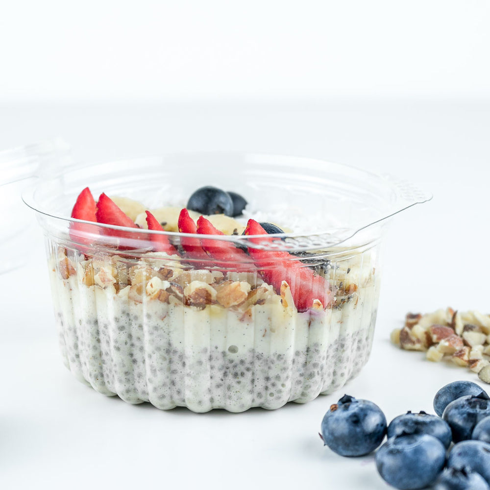 a chia pudding topped with almonds, banana, blueberries, strawberries, coconut flakes and chia seeds.