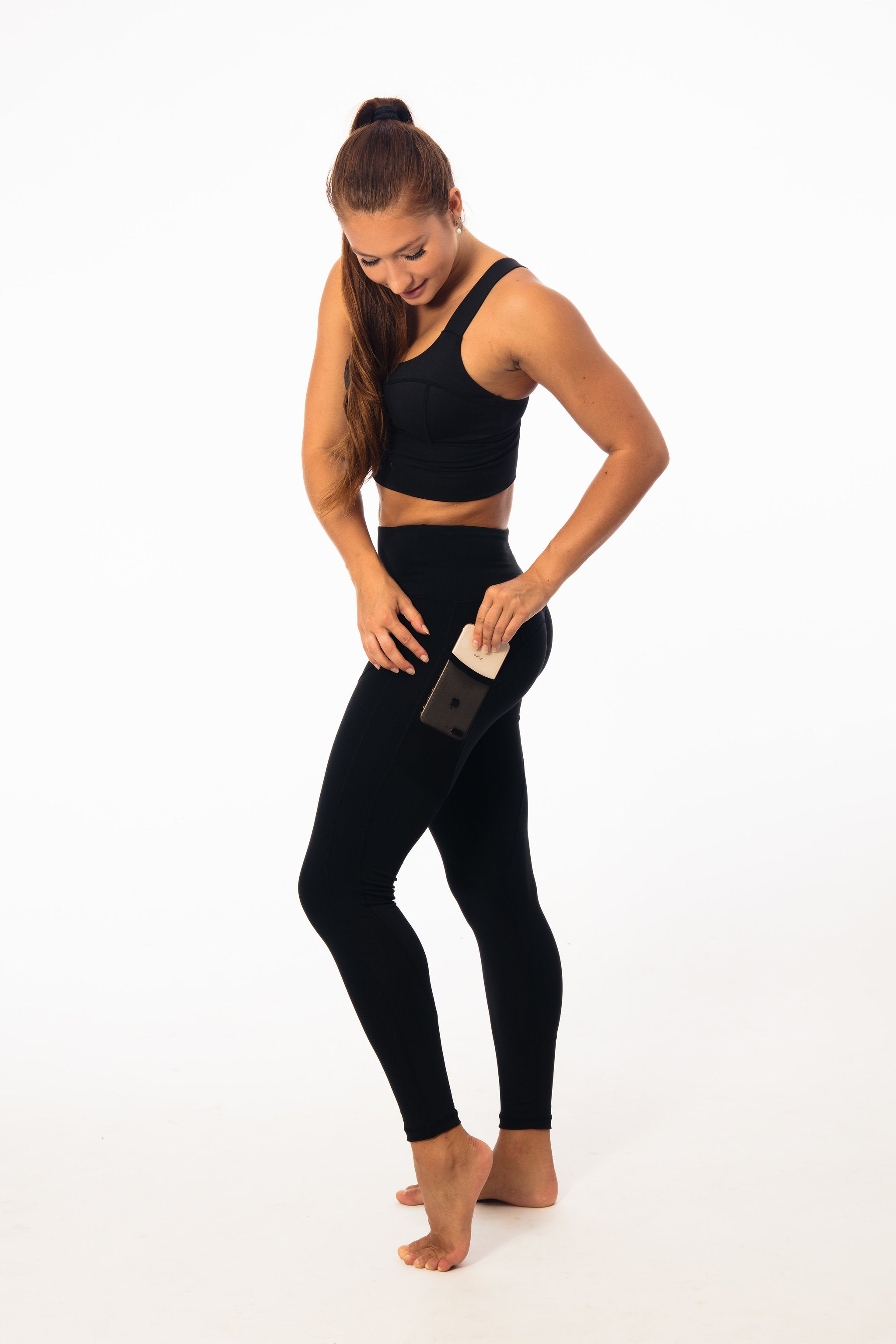 brunette wearing black leggings with a pocket and small tight tank top