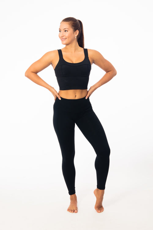 girl wearing mid drift gym tank with black high waisted leggings