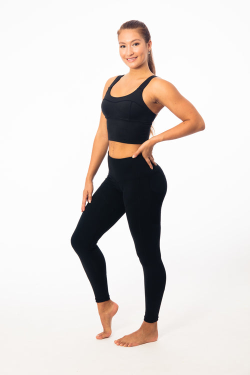 tall brunette wearing tight mid drift yoga top and black leggings