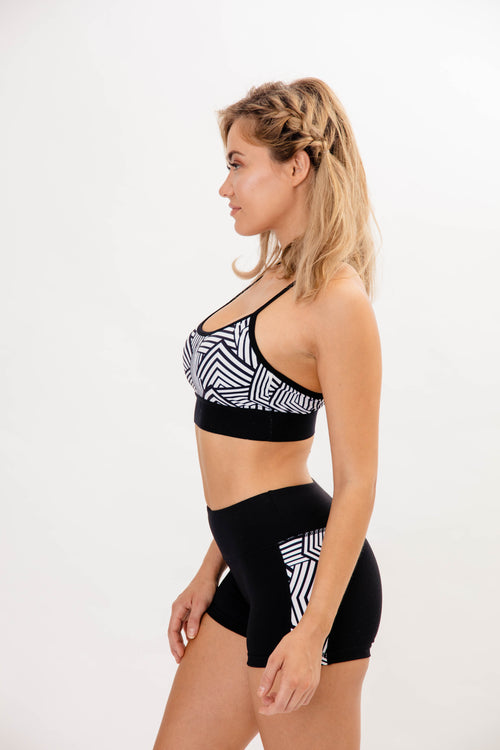 side view of brunette girl wearing black and white sports bra with matching yoga shorts