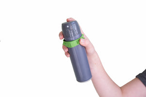 grey spray can held by a hand with green band around it