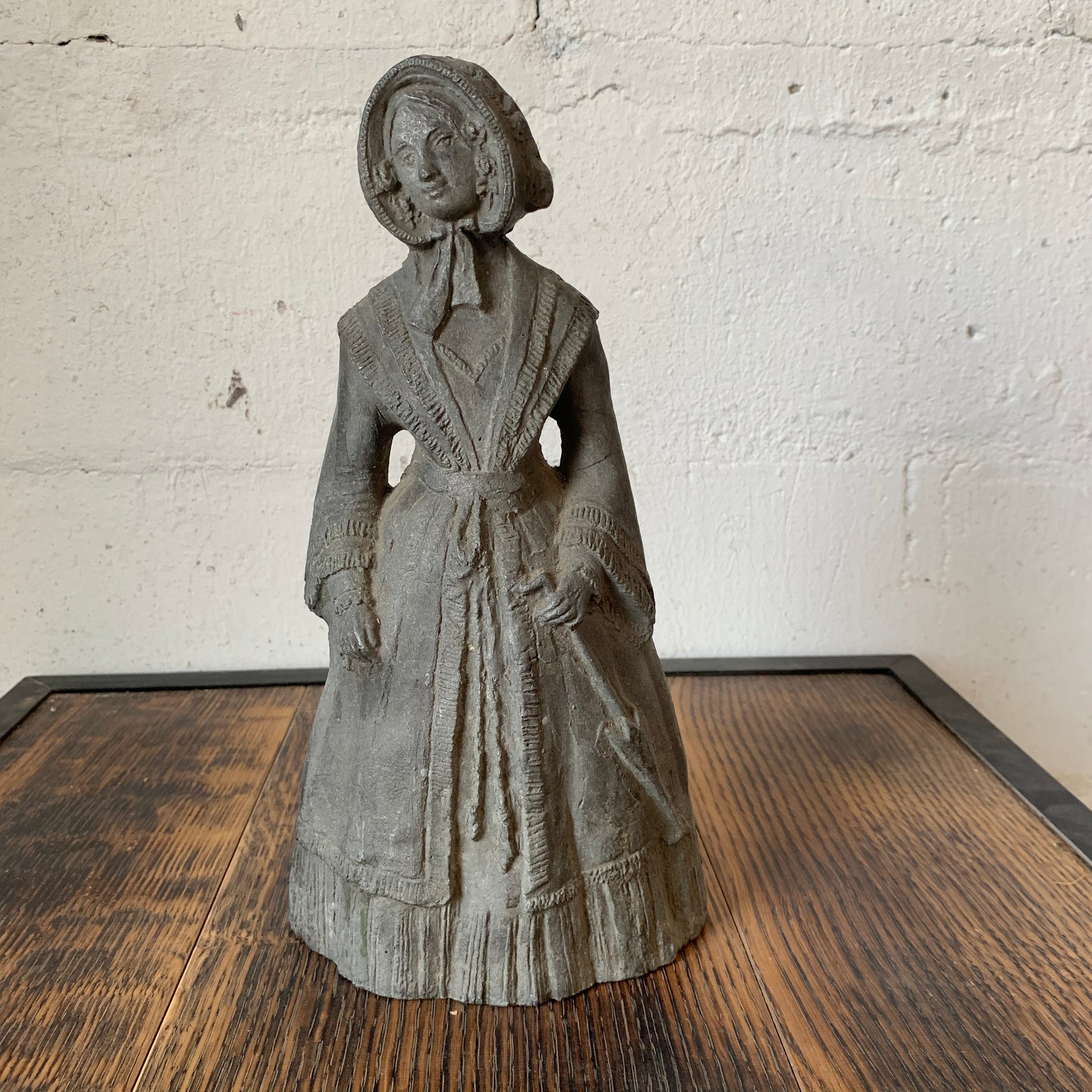 Antique iron doorstop in the shape of a peasant woman