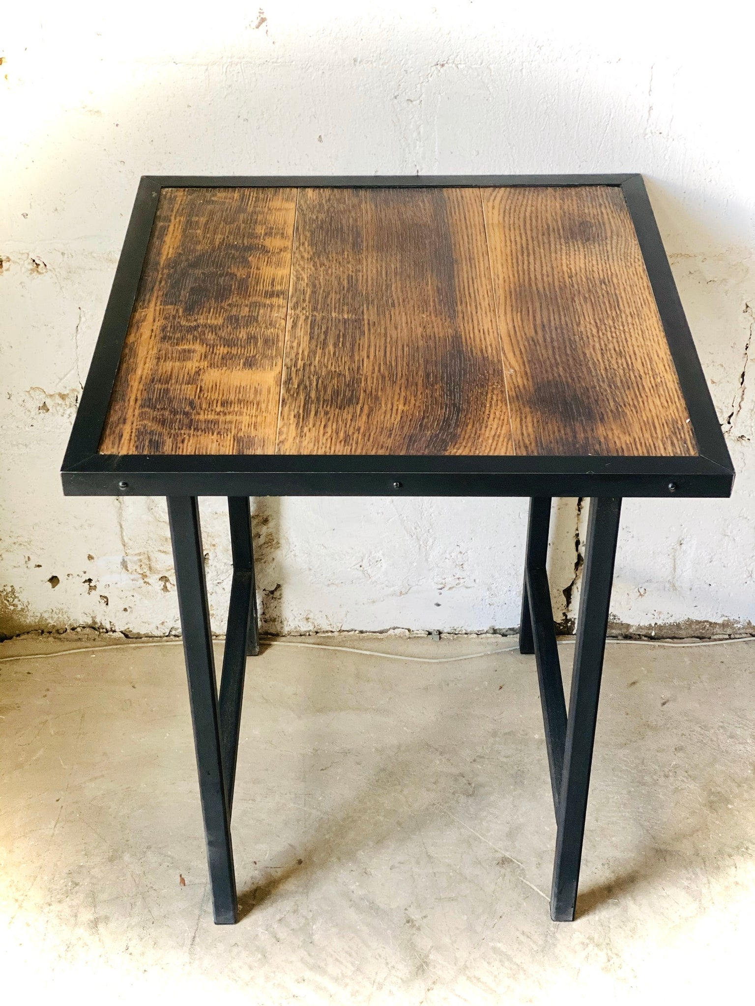 Made by Milne side table comprised of reclaimed flooring and blackened steel base with black steel edging