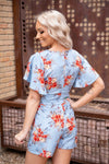 In Her Photographs Short Sleeve V-Neck Tie Waist Floral Romper in Blue - Filly Flair
