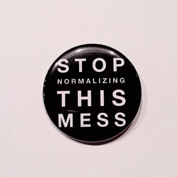 2.25 inch pinback button with text stop normalizing this mess printed in white letters with black background
