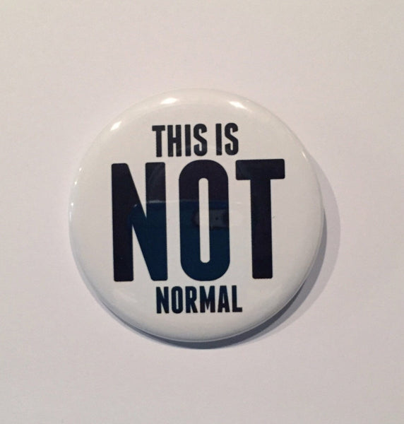 2.25 inch pinback button with This is not normal printed in black letters with white background