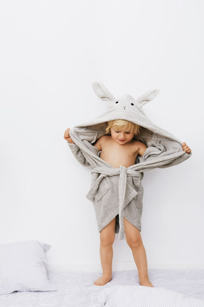 Toddler pulling off Liewood organic cotton grey rabbit bathrobe