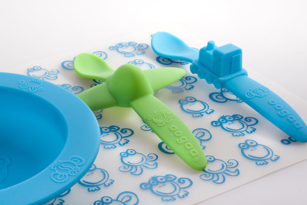 Oogaa blue placemat with Oogaa blue bowl, green plane spoon and blue truck spoon on top close up side view