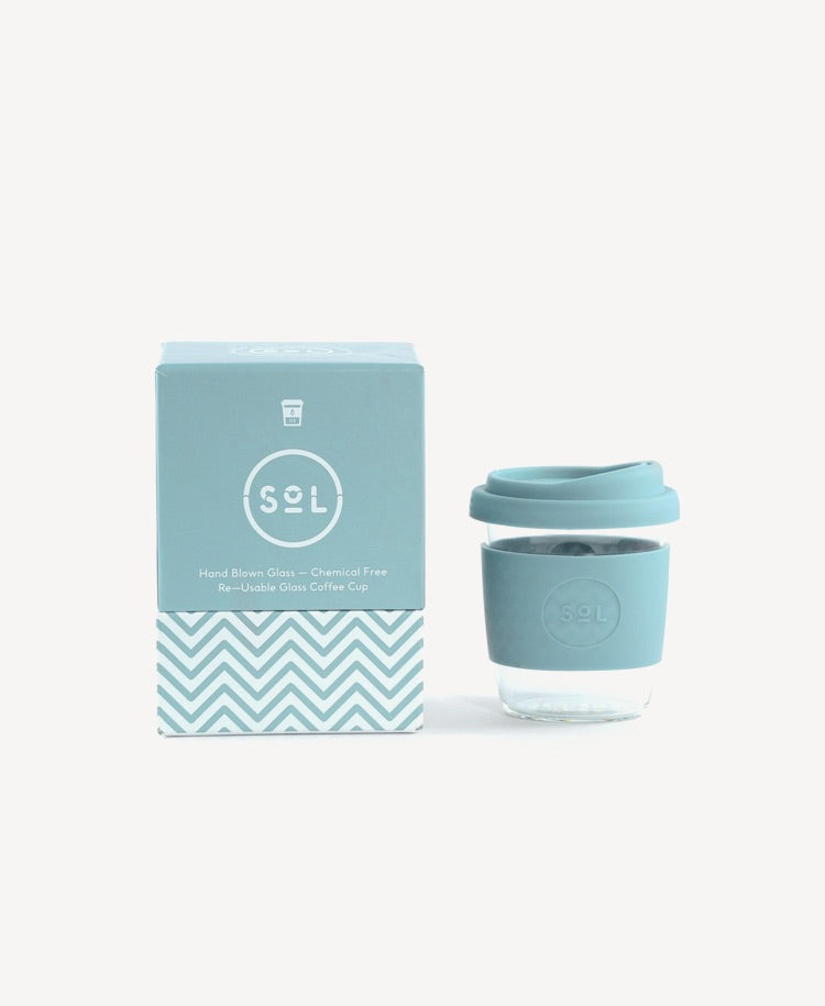 Sol glass Coffee Cup cool cyan next to packet front view