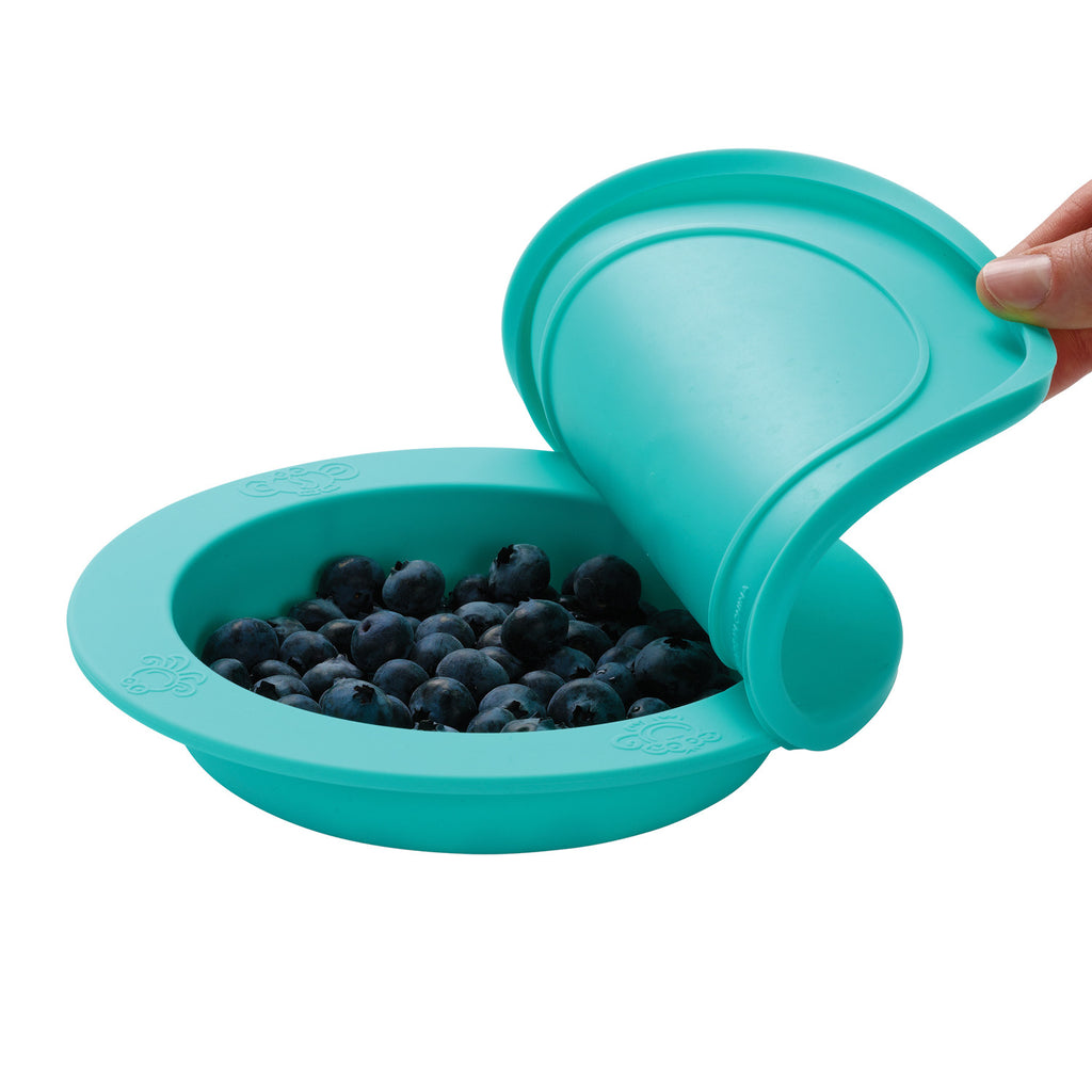 Oogaa jewel blue weaning bowl with blueberries inside and lid being peeled off side angle view