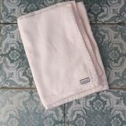 LittleHeart soft pink muslin folded on blue paisley tiled floor flatlay view