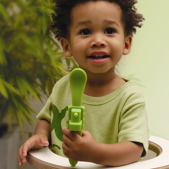 Oogaa green train weaning spoon held by toddler in high chair