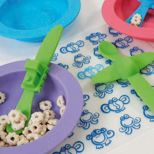 Oogaa green train weaning spoon in purple bowl of cereal on top of blue placemat with green plane spoon on it