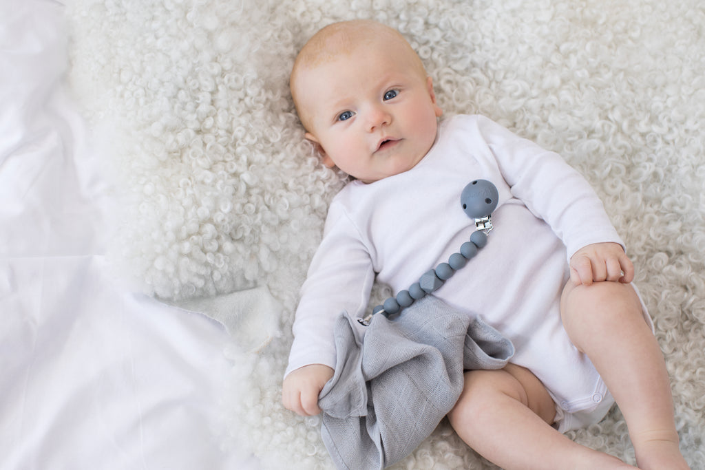 Baby lying on sheepskin rug with Les Enfants chewy dummy clip in grey on baby's tummy