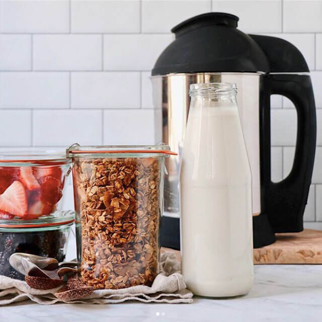 almond coconut granola in a jar next to a jug of milk
