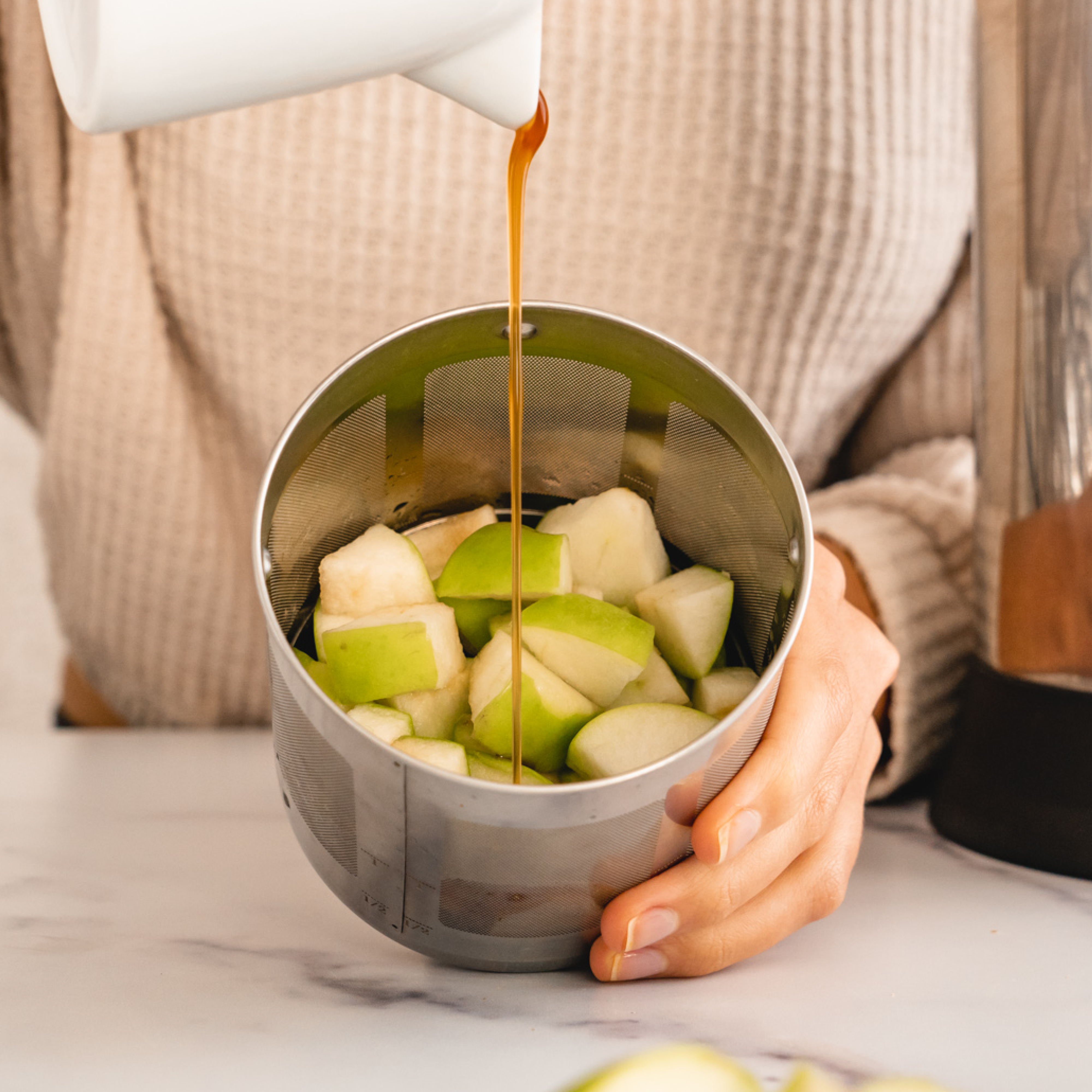 apples in a filter basket with vegan caramel being poured