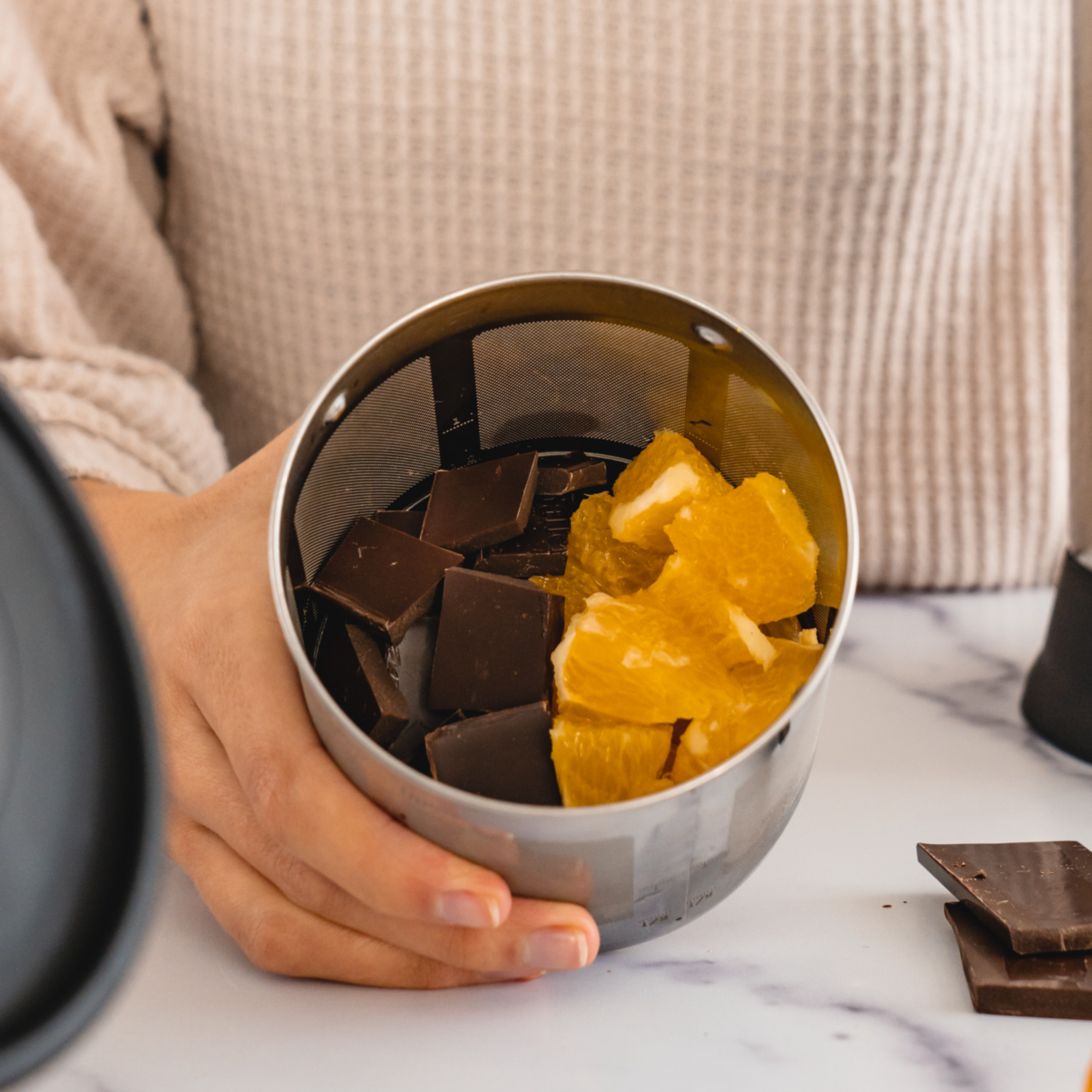 chocolate and orange slices in a filter basket of an Almond Cow