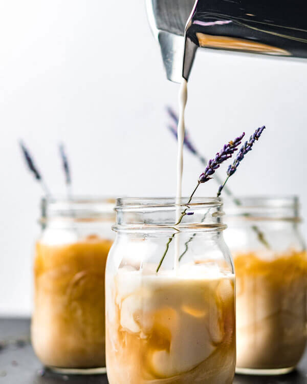 homemade vegan Iced Lavender Latte in a jar, with a sprig of lavender
