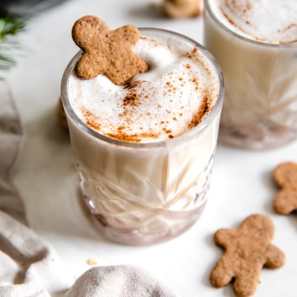 a glass of vegan oatnog with a gingerbread man