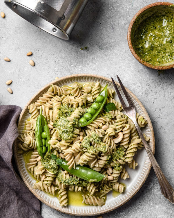 vegan pesto pasta on a plate with peas