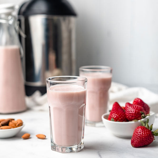 a jug and two glasses with homemade strawberry almond milk, next to almonds and strawberries