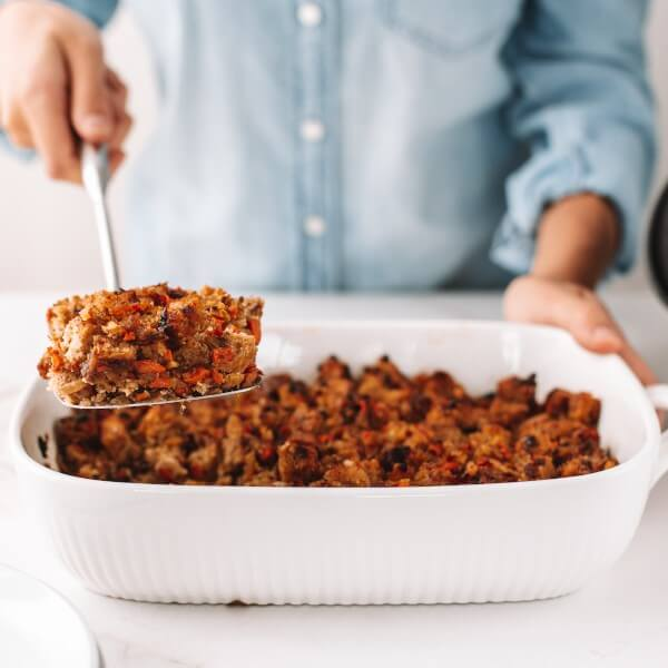 a person serving a baking tray of vegan stuffing