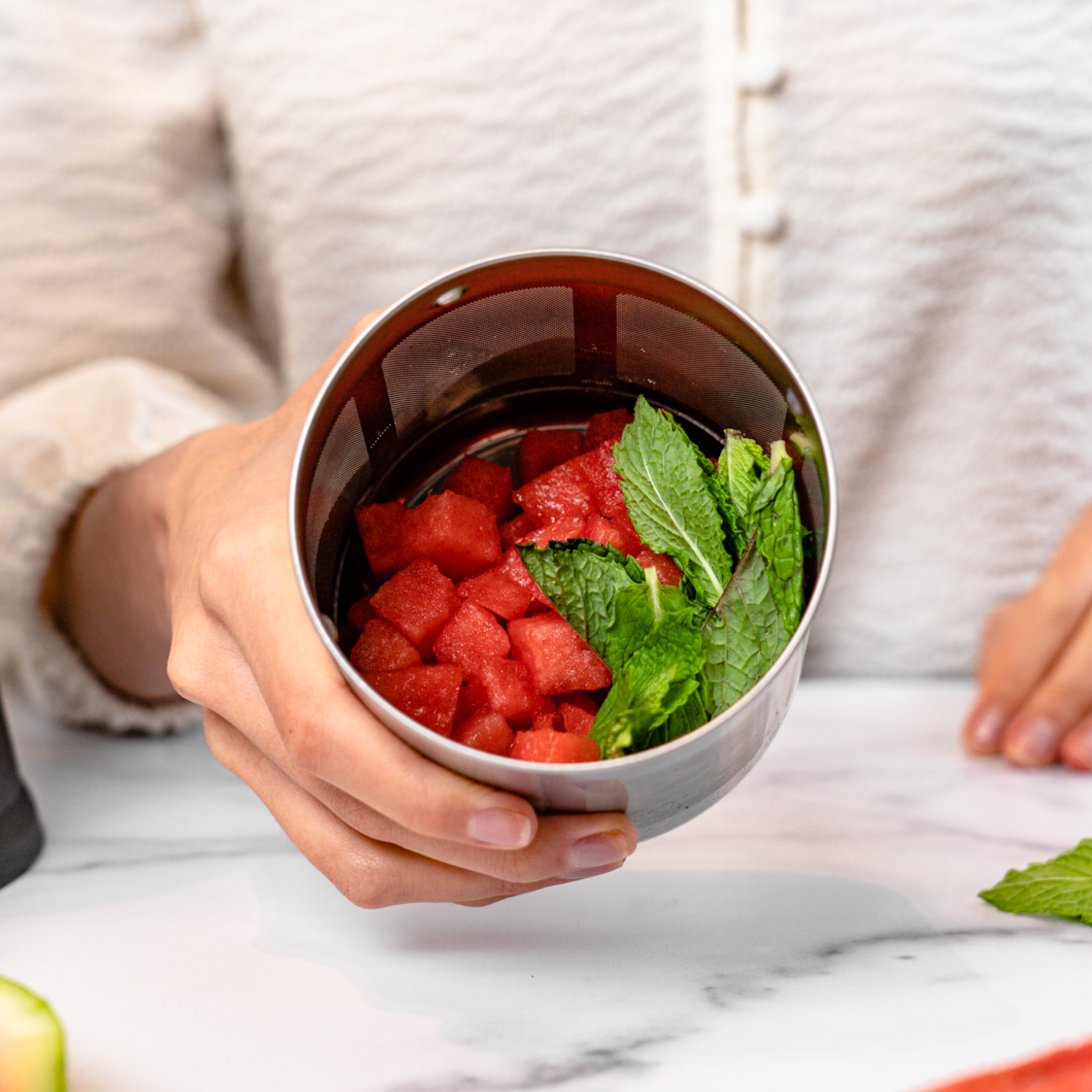 person holding filter basket full of watermelon and mint