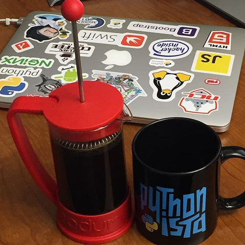 Pythonista Mug and a coffee maker in front of a laptop with stickers
