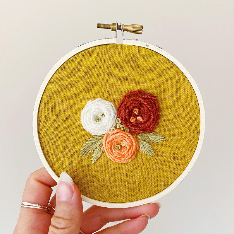 Flower Trio Hand-Stitched Embroidery - maroon, coral and white on mustard fabric.