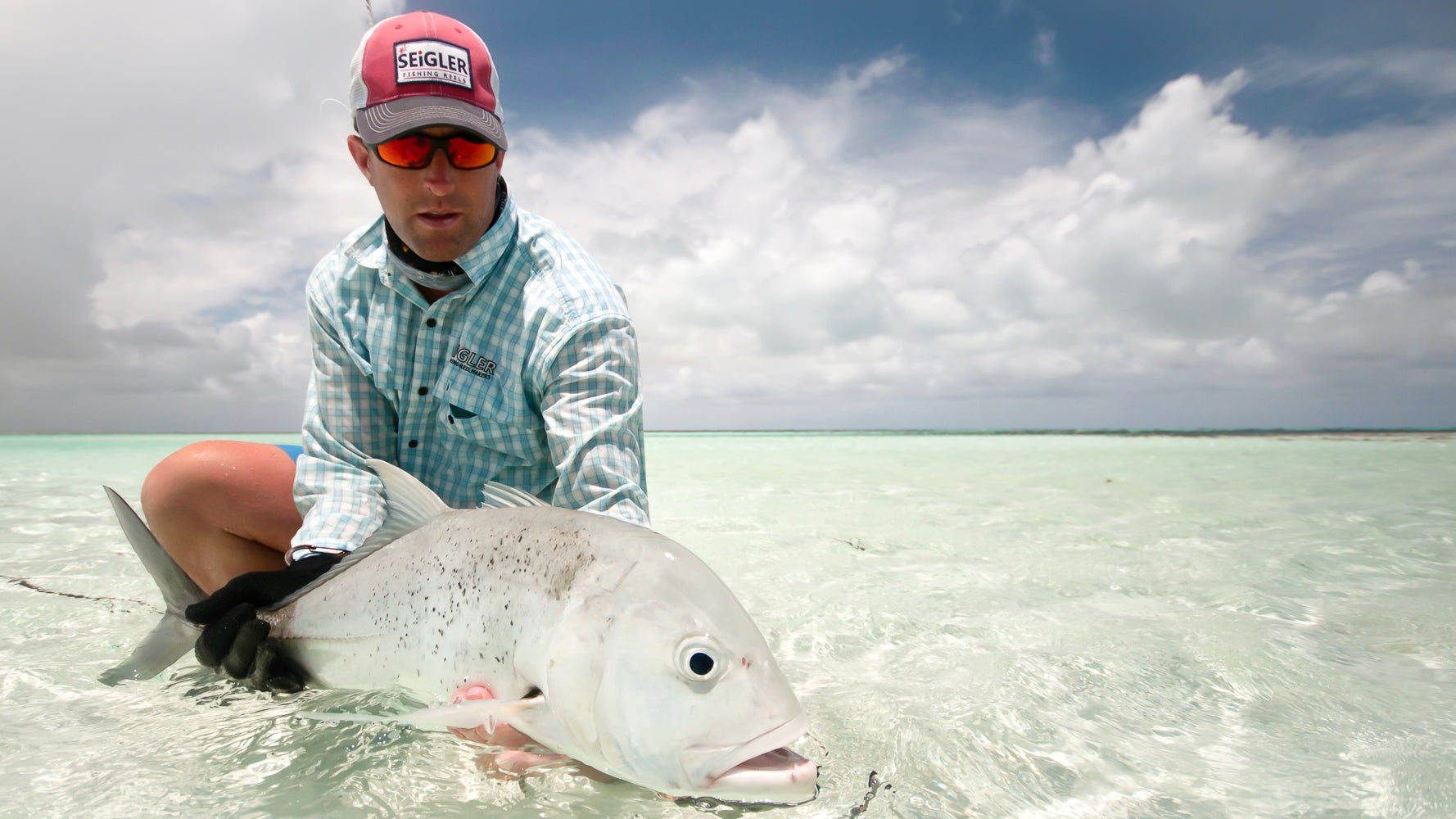 Wes Seigler holding a Giant Trevally caught on a saltwater fly reel.