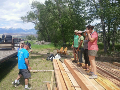 Friends help Sweet Belly Farm unload Timbers