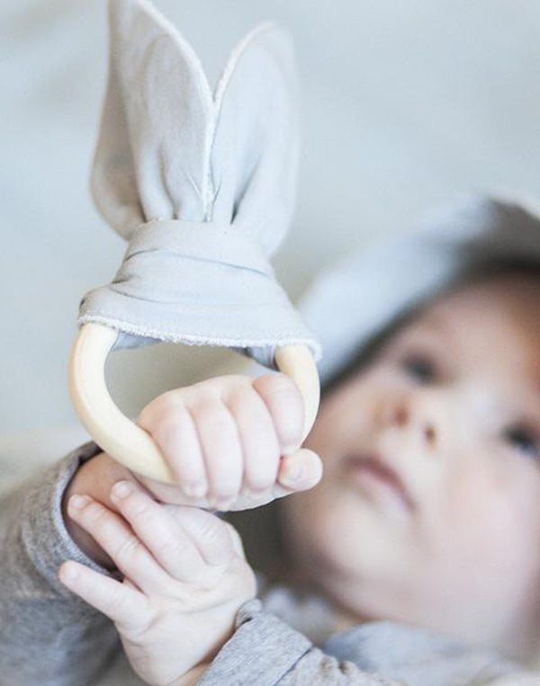Fabelab   Cute wooden baby teether with organic cotton bunny ears.   Size: 10 x 20cm. Ring dia. 7cm.  Color: grey, wood.  Composition: 100% GOTS certified organic cotton, terry backing, wooden ring.   Design from Denmark.