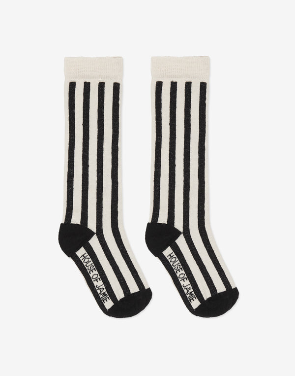 House of Jamie   Soft knitted knee socks with black- and cream colored vertical stripes. House of Jamie logo is knitted in the pattern on the bottom of the socks.  Color: Black, off white stripes.  Composition: 75% organic cotton 23% polyamide 2% elastane.