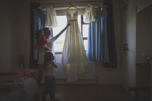 Wedding photograph of flowergirls looking at dress hanging up Galway Roscommon wedding photographer