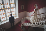 Galway wedding photography bride walking down staircase and groom looking out the window