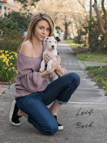 girl holding puppy with laid back look off the shoulder sweater and boyfriend jeans