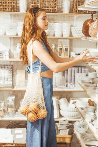 girl shopping in chambray two piece and basket of oranges