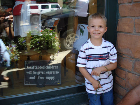 little boy in front of sign