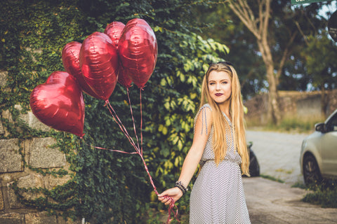 woman holding heart shaped balloons