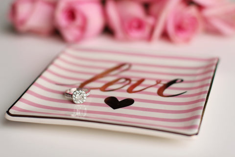 Engagement ring on a plate with the word love
