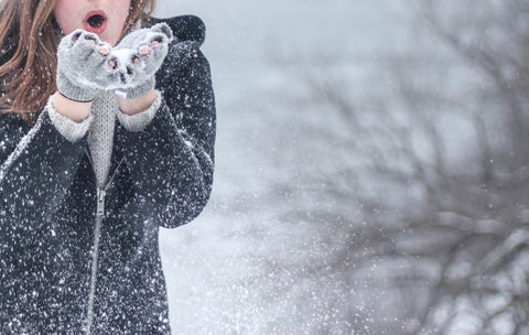 woman blowing snow in a winter storm
