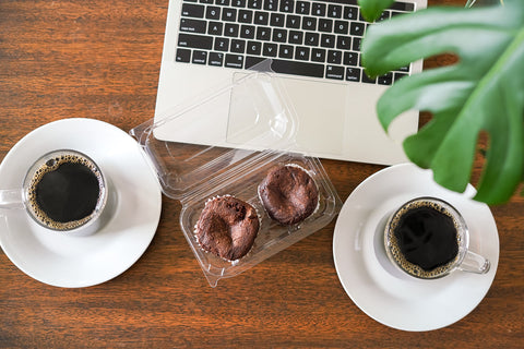 Nana Joes Granola Breakfast Brownies and a cup of coffee in front is a monstera leaf and a laptop