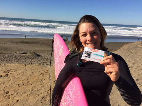 Bianca Valenti holding a pink surfboard and a Big Wave Bar
